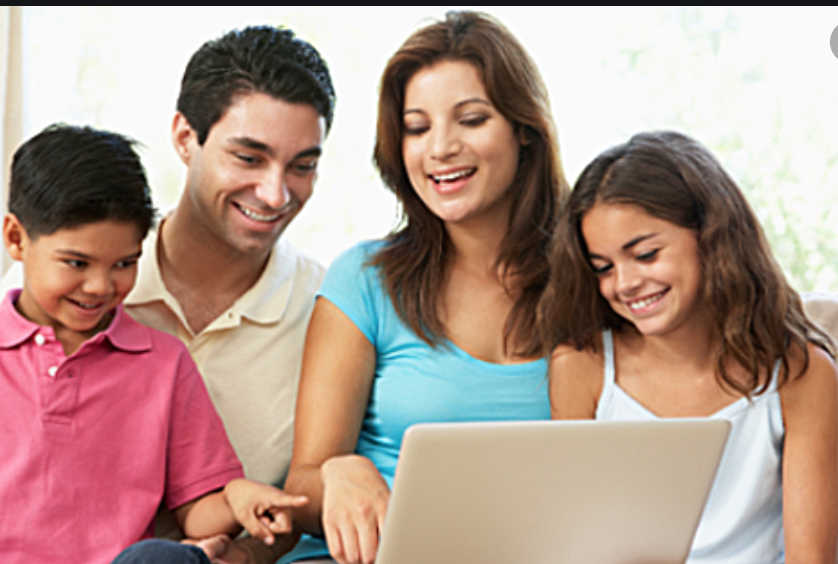 Family smiling at laptop screen